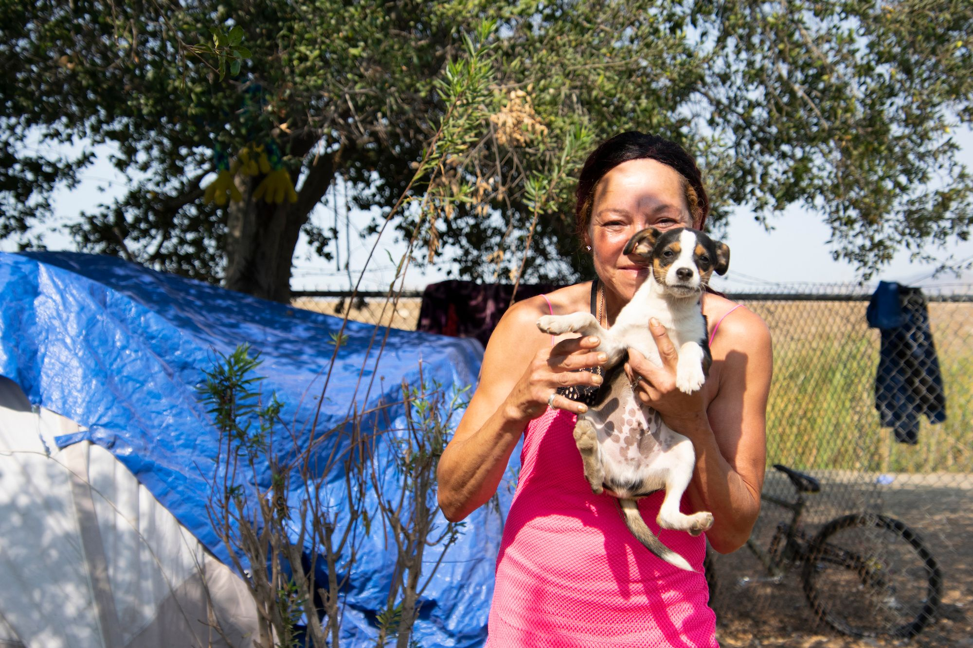 Tracy Harris, a resident of the homeless camp off Sacramento Street, holds up her dog.